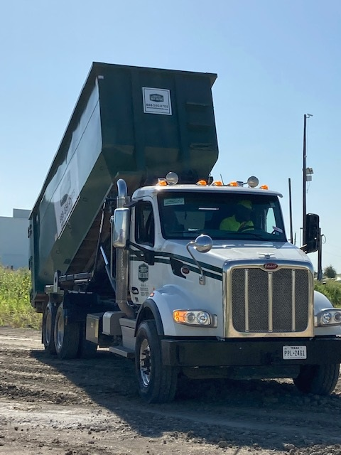 A Frontier Waste truck delivering a roll-off container