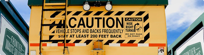 Caution sign on the back of a truck used for commercial trash service